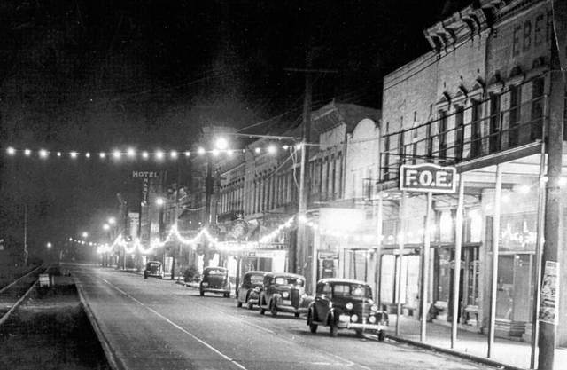This photo from the collection of Bob Graham shows Main Street in Pomeroy decorated for Christmas in 1938. Lights hang along the right side of the photo as cars are parked in front of the downtown businesses, while the street car tracks can be seen on the left side of the photo. Among the buildings pictured is the Hotel Martin.
