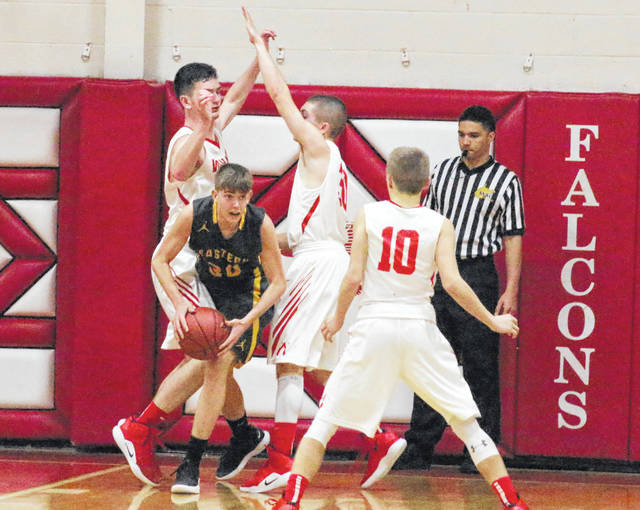 Eastern junior Garrett Barringer (30) is double-teamed by Wahama defenders Adam Groves and Jacob Lloyd during the second half of Tuesday night's boys basketball contest at Gary Clark Court in Mason, W.Va.