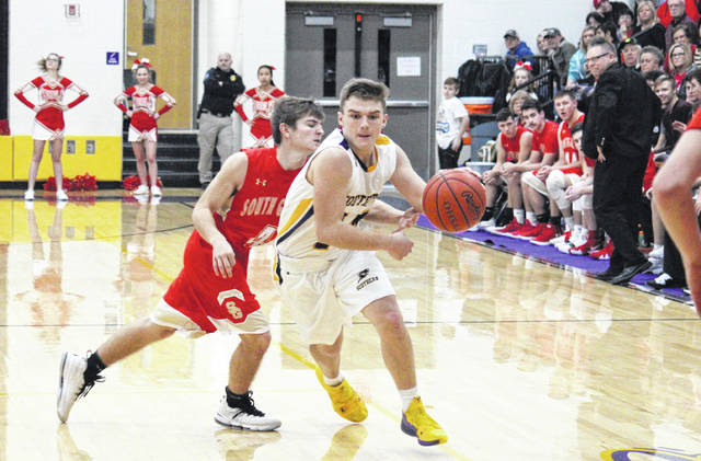SHS junior Trey McNickle drives past SGHS senior Garrett Saunders (4), during the Tornadoes' 68-54 victory on Tuesday in Racine, Ohio.