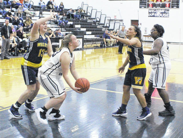 River Valley junior Kaylee Tucker, with ball, prepares to release a reverse layup attempt between a pair of Wellston defenders as teammate Destiny Dotson looks on during the second half of Thursday night's girls basketball contest in Bidwell, Ohio.