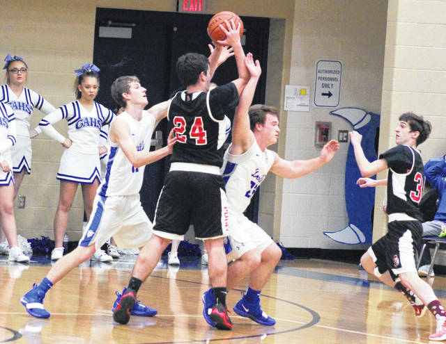 Gallia Academy senior Blaine Carter, left, applies pressure to Point Pleasant's Braxton Yates (24) during the first half of Saturday night's boys basketball contest in Centenary, Ohio.
