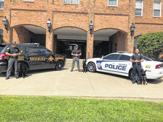Gallia Sheriff's Office's Gary Waldron and Thunder, Gallia Sheriff Matt Champlin and Gallipolis Police Patrolman Mark Still with Gina stand in front of the Gallia Courthouse.