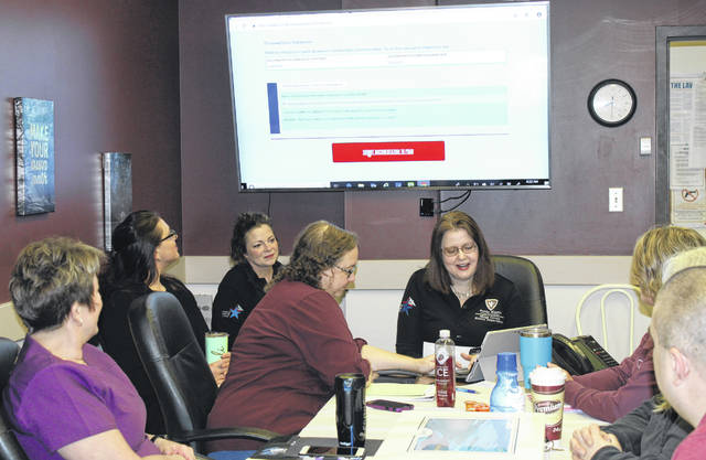 Accreditation Coordinator Michelle Willard and Administrator Courtney Midkiff press the button to submit the accreditation documents during Wednesday's staff meeting at the Meigs County Health Department.