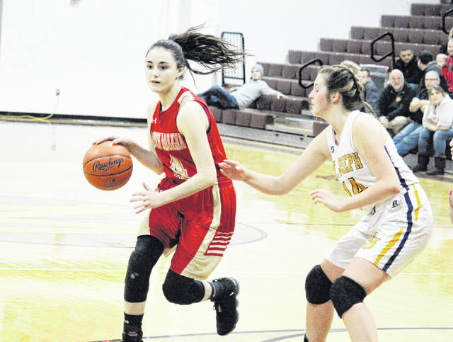 South Gallia junior Kiley Stapleton (4) drives past St. Joseph junior Faith Mahlmeister (14), during the Division IV sectional semifinal on Wednesday in Rocksprings, Ohio.