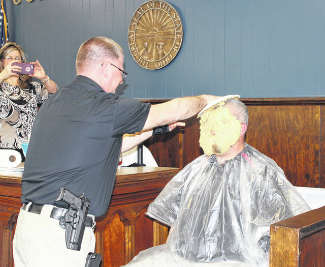 Major Scott Trussell rubs the whipped cream pie through Commissioner Randy Smith's face and hair.