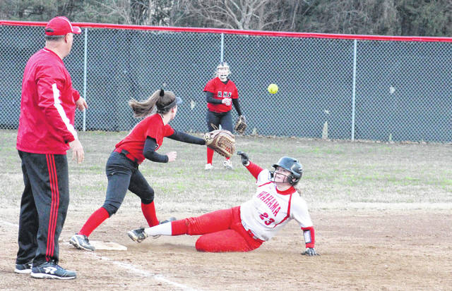 Wahama senior Maddy VanMatre (23) slides safely into third base in front of first-year WHS head coach Chris Noble (left), during the Lady Falcons' 10-4 win on Thursday in Ravenswood, W.Va.