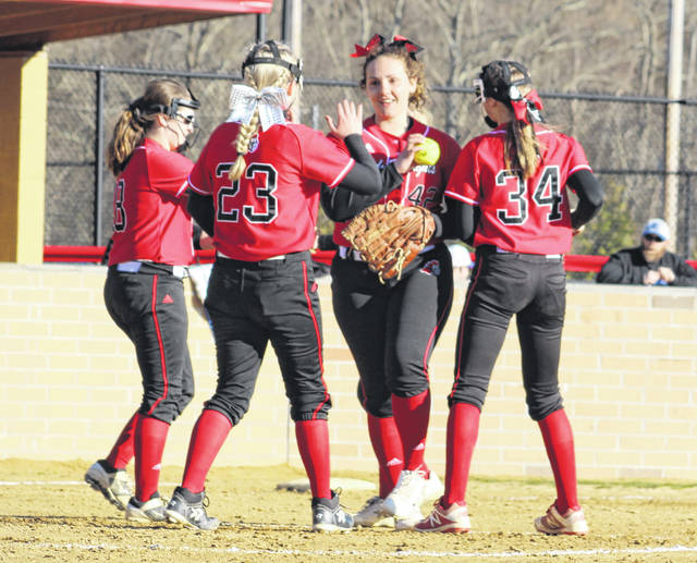 Point Pleaasant starting pitcher Rylee Cochran, middle, receives some high-fives from teammates after a second inning strikeout Tuesday night in a non-conference softball contest against Ripley in Point Pleasant, W.Va.