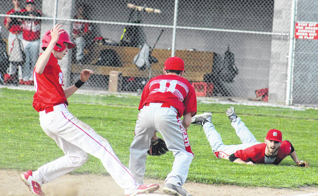 Wahama senior Cooper Peters (left) makes it safely to third base, before Max Hooper's (right) diving throw reaches Landon Wisor (11), during the White Falcons' 10-0 victory on Wednesday at Claflin Stadium in Mason, W.Va.