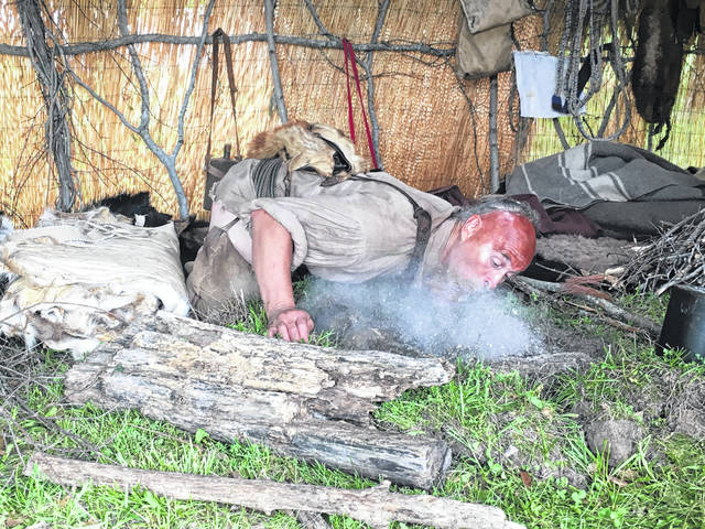 The reenactors take on the lives of their characters the entire weekend they stay at Fort Randolph. Pictured is a Native American re-enactor making a fire.