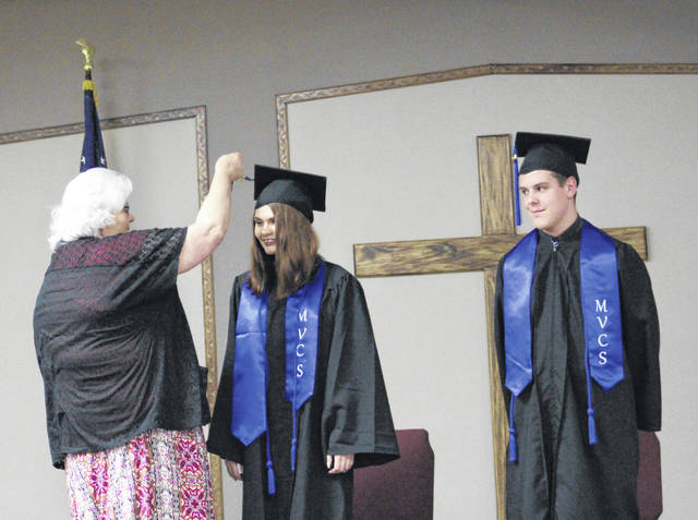 Maggie Biggs completes the turning of the tassels for graduates Melyla Mash and Miciah Swab.