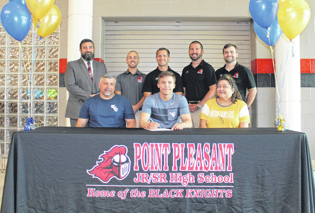 Point Pleasant senior George Smith, seated center, will be continuing his wrestling career after agreeing to become a preferred walk-on at West Virginia University on Thursday, May 23, at the PPHS Commons Area in Point Pleasant, W.Va. George Jr. is joined by his parents, George and Annette Smith, at the table. Standing in back, from left, are PPHS Principal Bill Cottrill, PPHS assistant David Bonecutter, PPHS wrestling coach John Bonecutter, PPHS assistant Jed Ott and PPHS assistant James Casto.