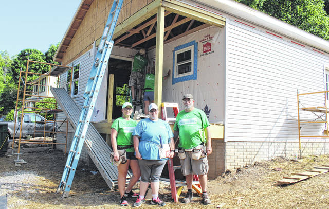 Volunteers Pam Muncy and Mitch Smith from Pleasant Valley Hospital are pictured with homeowner Aja Collins at the new Habitat for Humanity House.