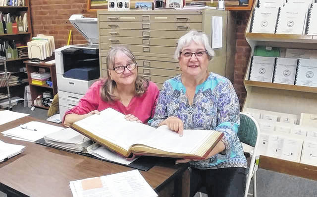 Gallia Historical Society's Cheryl Enyart, left, assists researcher Lisa Haschart, right.