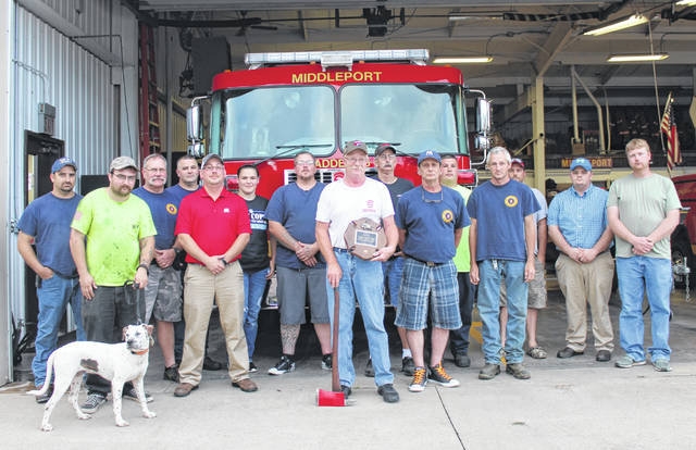 """Middleport Fire Chief Jeff Darst was recognized following the department's meeting on June 20 for 45 years of service to the Middleport Volunteer Fire Department. Darst has been an active member of the fire department for 45 years, having been around the department for several years growing up prior to officially joining the department. Darst's father was also a member of the Middleport Volunteer Fire Department, leading to the now-Chief spending much time at the station from a young age. """"It's something I loved to do all my life,"""" said Darst. Darst was presented with a plaque and an ax to commemorate his years of service to the department. Darst is pictured with department members in attendance, from left, John Bentz, Jesse Pullins, canine Rommel, Larry Byer, Shannon Smith, Chris Snouffer, Alicia Smith, Charles Uhlig, Jeff Darst, Joe Anthony, Joe Powell, Jordan Shank, Michael Klein, David Heighton, Clayton Taylor and Gene Bing. In the second photo, Darst is presented a plaque by firefighter Joe Powell."""