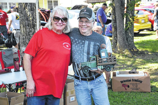 Linda Blosser is pictured presenting the trophy for Best of Show to Terry Shain and his 1971 White Chevy Pickup.