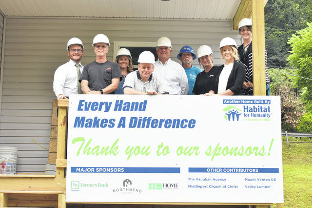 Pictured on the porch of the new Habitat for Humanity House are (left to right) Dru Reed, Tim King, Shelly Combs, David Hopkins, Paul Reed, Bryan Smith, Missy Best, Caitlyn Moritz, and Chelsie Frazier.