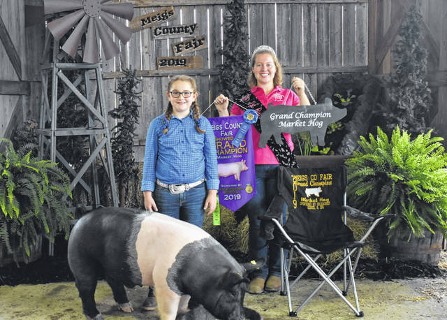 Kristina Weakley is pictured with her Grand Champion Market Hog. Also pictured is Fair Queen First Runner-Up Raeven Reedy.