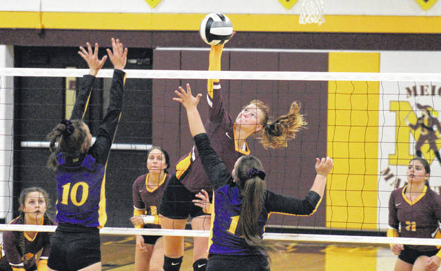 Meigs sophomore Mallory Hawley attempts a spike over a pair of Lady Tornadoes, during the Lady Marauders' season-opening win over Southern on Tuesday in Rocksprings, Ohio.