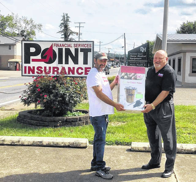 "During the Mason County Fair, Larry Jones, owner of Point Financial Services Insurance, pictured at right, held a drawing for an old fashioned ice cream freezer. The winner, Dwayne Baker is pictured accepting his prize from Jones. ""Congratulations to Mr. Baker and thank you to everyone who stopped by the PFS Insurance booth during the fair,"" stated Jones."