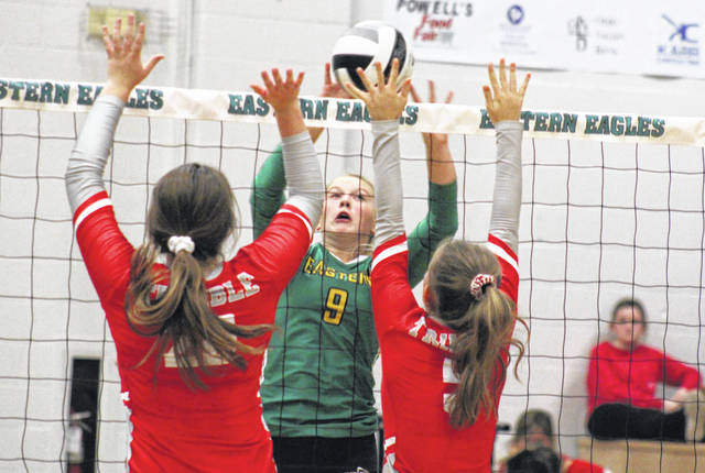 Eastern junior Tessa Rockhold (9) tips the ball over a pair of Lady Tomcats, during Trimble's 3-2 victory on Tuesday in Tuppers Plains, Ohio.