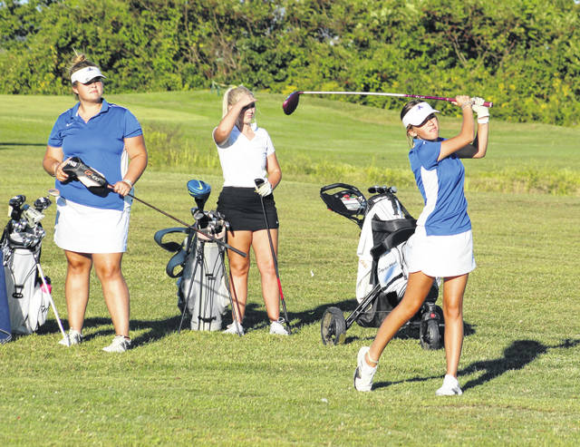 Gallia Academy junior Avery Minton, right, watches a tee shot take flight during a match Thursday at Cliffside Golf Course in Gallipolis, Ohio.