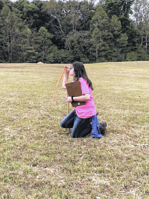 Mallory Stover is pictured measuring the slope of the land.