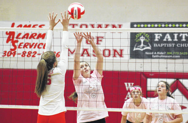 Wahama freshman Hailey Durst (31) tips the ball over a Calhoun County defender, in front of teammates Emma Gibbs (14) and Mary Roush (right), during the Lady Falcons' 3-0 loss on Tuesday in Mason, W.Va.