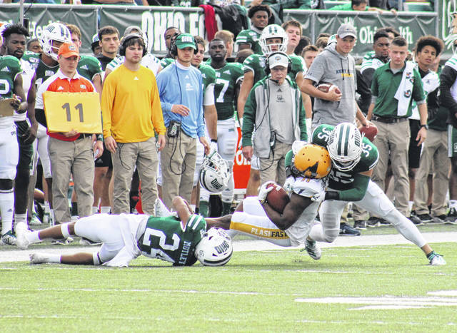 Ohio defensive backs Xavior Motley (24) and Dylan Conner (35) bring down a KSU receiver in front of the Bobcat sideline, during Saturday's MAC East showdown at Peden Stadium in Athens, Ohio.