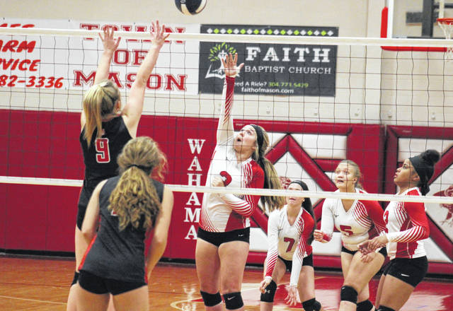 Wahama's Jessica Dangerfield (center) attempts a spike over a Ravenswood defender, during the Lady Falcons' 3-0 victory on Tuesday in Mason, W.Va.