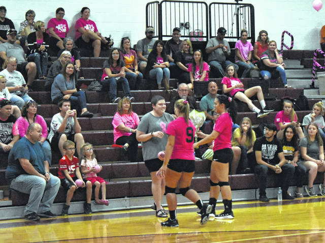 Members of the Meigs Volleyball Team present Andrea Clegg with flowers during the Volley for the Cure game at Meigs High School on Oct. 3.
