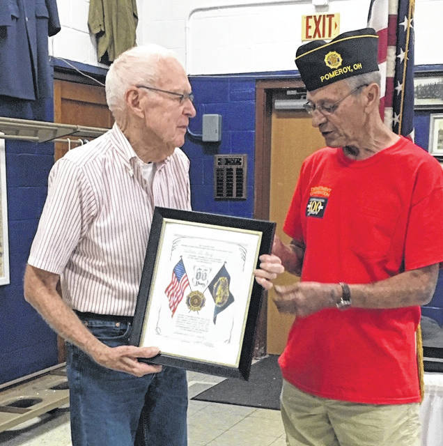 William H. King receives a plaque for 65 years of membership in the American Legion from Post Commander John Hood.