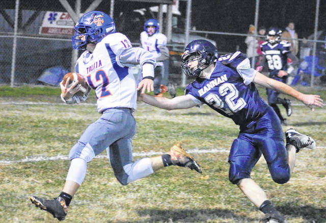 Hannan senior Jordan Fitzwater (22) tries to grab ahold of Tolsia ball carrier Jesse Muncy (12) during the first half of Friday night's Week 11 football contest in Ashton, W.Va.