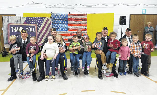 """Carleton School and Meigs Industries joined together for a Veterans Day celebration on Monday, honoring those who have served in the branches of the United States military. The veterans held a small ceremony around the flagpole and shared their service dates and assignments. Students sang """"You're a Grand Old Flag"""". Pictured are Carleton Preschool students who presented the veterans with handmade cards and a small gift."""