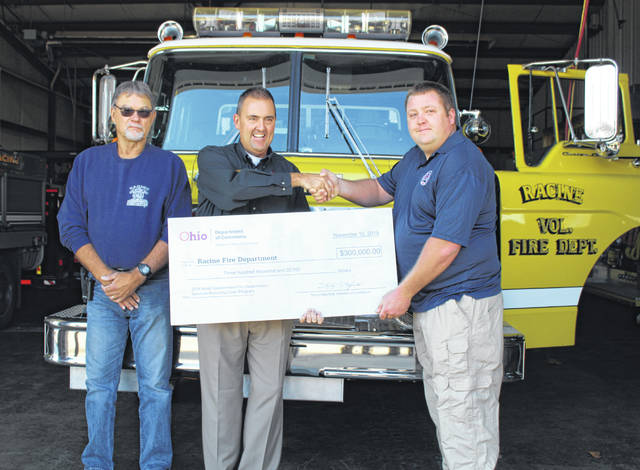 Captain David Neigler (left) and Firefighter Ian Wise (right) from the Racine Volunteer Fire Department accepted a check from Chief Deputy Bill Spurgeon of the Ohio Fire Marshal's Office representing the $300,000 no-interest loan which is to help with the purchase of a new pumper truck.