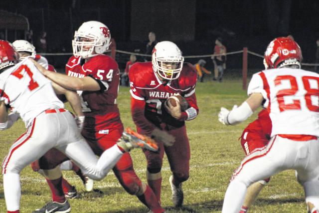 Wahama senior Nick Brewer (center) carries the ball behind a block from freshman Michael VanMatre (54) during the White Falcons' 79-0 loss on Friday in Mason, W.Va.