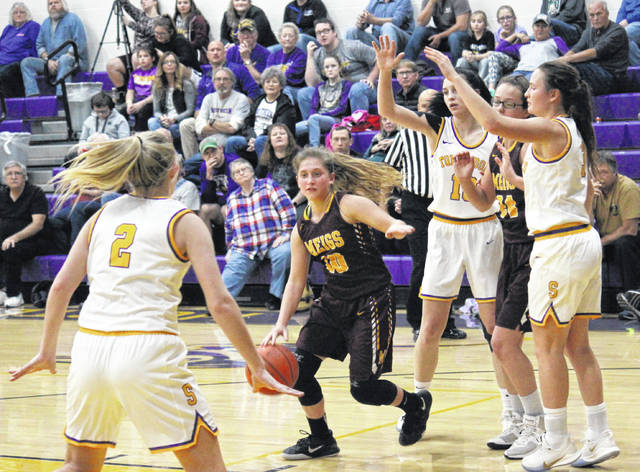 Lady Marauders guard Bre Lilly (10) drives to the basket in front of teammate Mara Hall (24), and in between Lady Tornadoes Shelby Cleland (2) Jordan Hardwick and Baylee Wolfe (right), during the Lady Marauders' 13-point victory on Wednesday in Racine, Ohio.