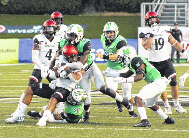 Marshall linebacker Omari Cobb (31) joins Domenick Murphy (40) in bringing down a Cincinnati running back during a Sept. 29 football game at Joan C. Edwards Stadium in Huntington, W.Va.