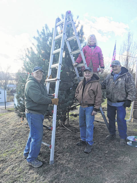 Chester Shade Historical Association members put up a Christmas tree in front of the Chester Courthouse in preparation for Saturday's Open House. Pictured (from left to right) are Dan Will, Dave Schatz, Jim Smith, with Opal Grueser on the ladder.