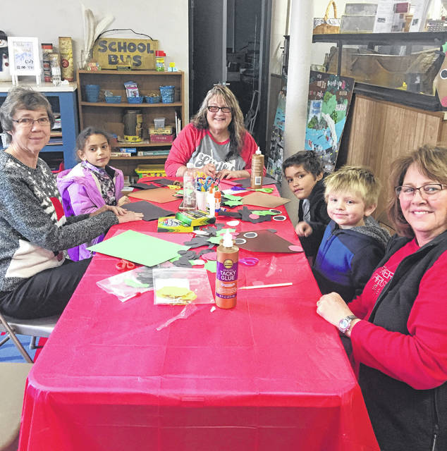 Museum volunteers assist children with crafts as part of Kids' Day at the Museum. Pictured are (top center) museum volunteer Debbie Pratt, (left) Lorelei Burnett, museum volunteer Patty Grossnickle, (right) Debon Burnett. Elijah Laides, and museum volunteer Betsy Jones.