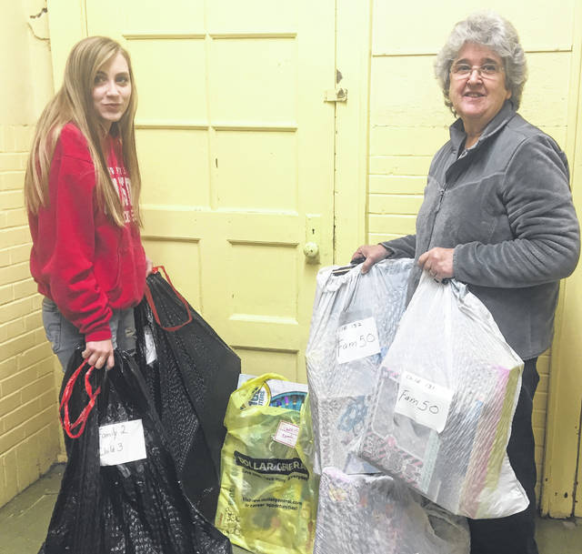 Maddie Null helped her grandmother Janice Middleton prepare items for pickup last Saturday at Hearts and Hands Thrift Store.