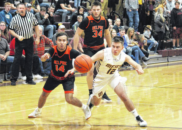 Meigs senior Cory Cox (12) gets a loose ball in front of Golden Eagles Logan Adams (14) and Nick Godfrey (34), during the Marauders' 65-61 victory on Tuesday in Rocksprings, Ohio.