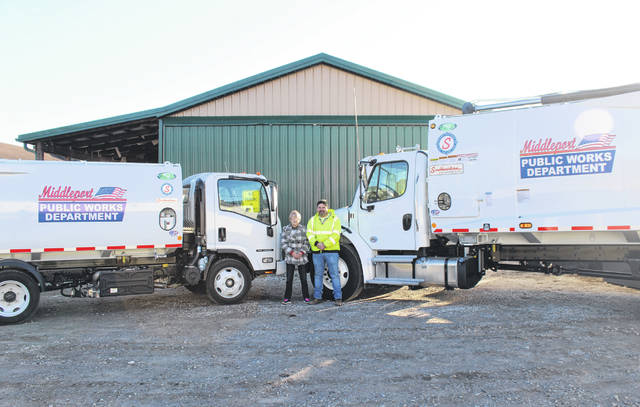 Village administrator Joe Woodall and then Mayor Sandy Iannarelli are pictured with the two new trash trucks purchased by the village.