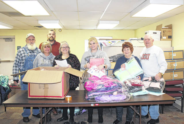 Representatives from Trinity Congregational Church recently sorted coats which will be delivered to area children. Pictured (from left to right) are John Seelhorst, Marylin Seelhorst, Randy Smith, Linda Warner, BJ (Smith) Kreseen, Carol Adams, and Floyd Chapman, all of Trinity Congregational Church