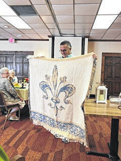 Melvin Biars of Floral Fashions in Gallipolis holding a fleur di lei throw blanket given to Sheryl Fallon as a door prize.