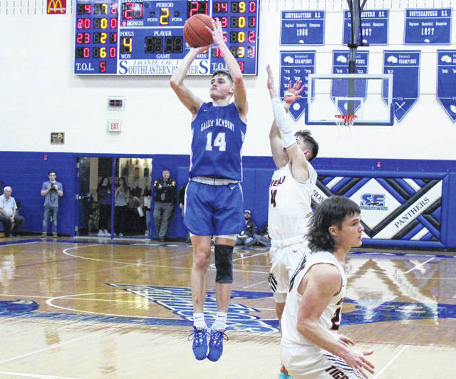 Gallia Academy senior Logan Blouir (14) releases a shot attempt over a Waverly defender during the first half of Tuesday night's Division II boys basketball sectional semifinal at Southeastern High School in Londonderry, Ohio.