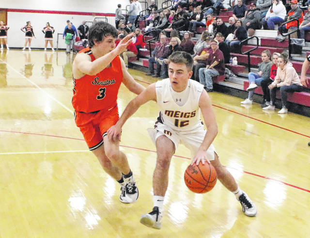 Meigs senior Cory Cox (12) dribbles past a Portsmouth West defender during the second half of a Division III sectional semifinal boys basketball contest at Jackson High School on Feb. 19 in Jackson, Ohio.