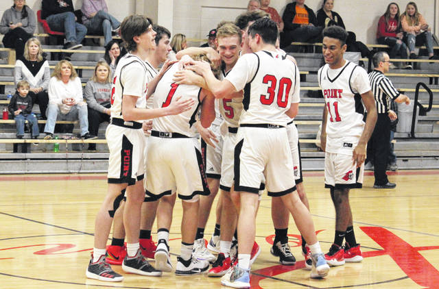 Members of the Point Pleasant boys basketball team celebrate PPHS junior Hunter Bush (1) surpassing the career 1,000-point plateau, during the Big Blacks' 81-41 victory on Tuesday in Point Pleasant, W.Va.