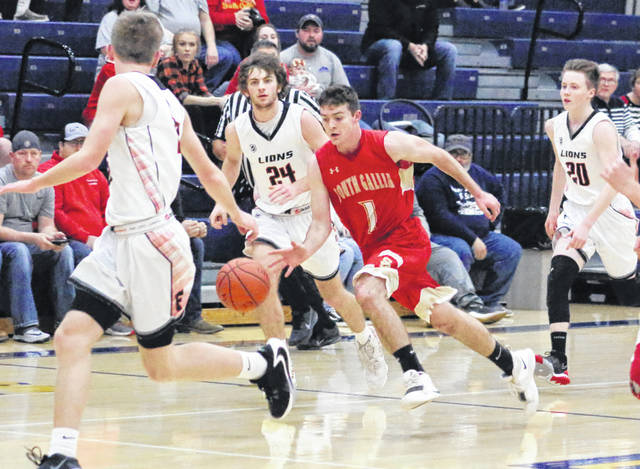 South Gallia senior Kyle Northup (1) dribbles the ball between a trio of Fairfield defenders during the first half of Tuesday night's Division IV boys basketball sectional final at Wellston High School in Wellston, Ohio.