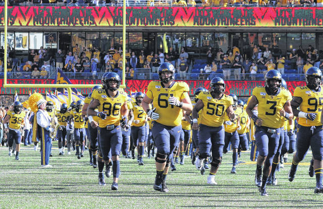 Members of the 2019 West Virginia Mountaineers run onto the field prior to their a Big 12 game against Texas on Oct. 5 in Morgantown, W.Va.