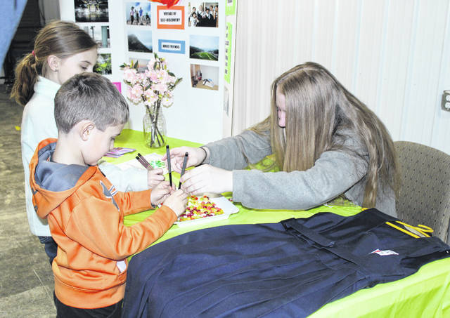 Kyra Zuspan teaches young attendees how to use chopsticks. Zuspan spent time last summer as part of the 4-H Exchange Program in Japan.
